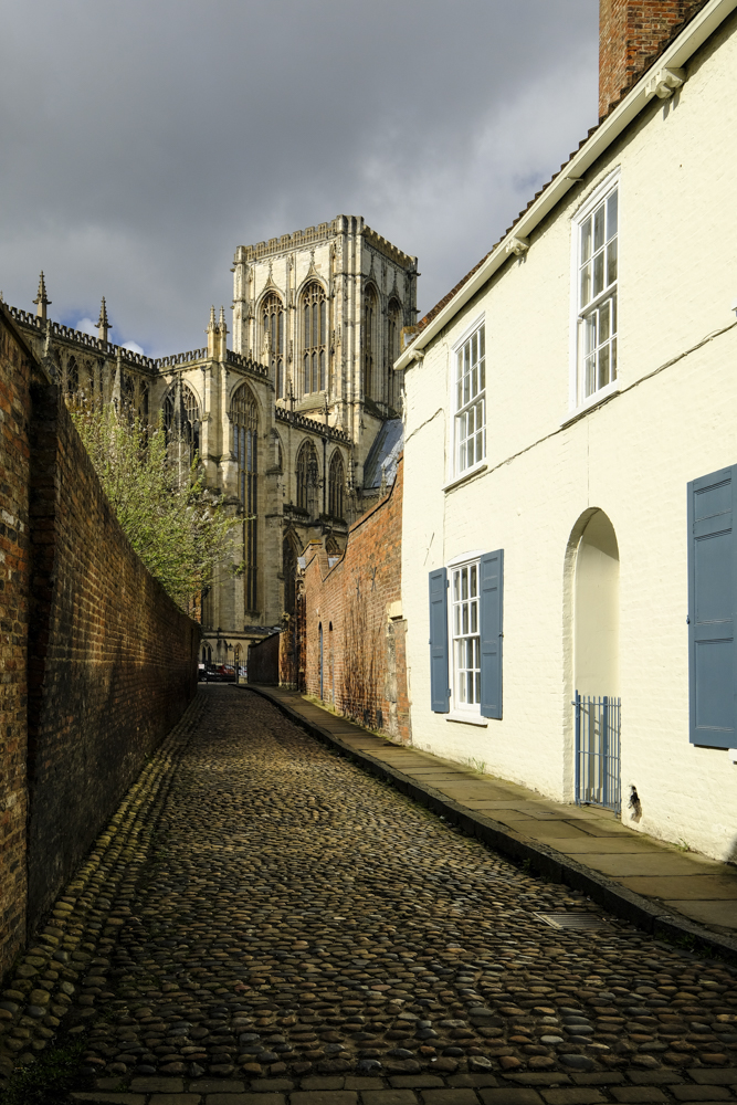 View along the ancient cobbles of Chapter House Street towards York Minster.