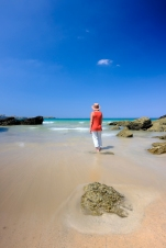Woman standing in shallow water on a beautiful beach in Cornwall