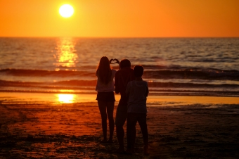 Young women making a heart shape with her hands as the sun sets on Portmeor Beach in St Ives, Cornwall