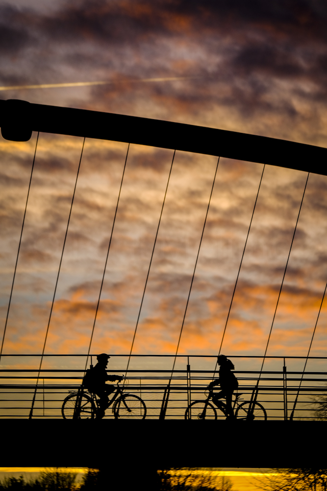 Two cyclists silouetted against the sunset sky while crosing the Millennium Bridge in York, UK.