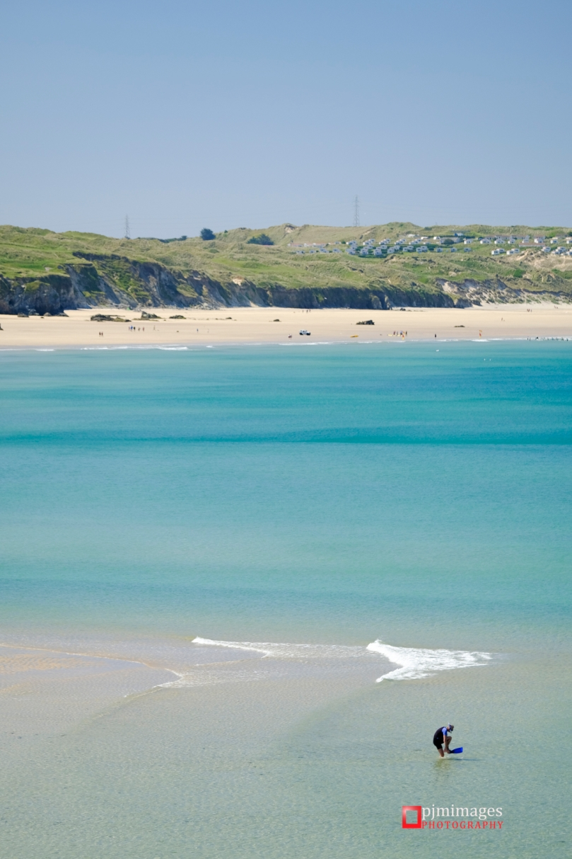 Man on Godrevy beach in the shallow water in Summer