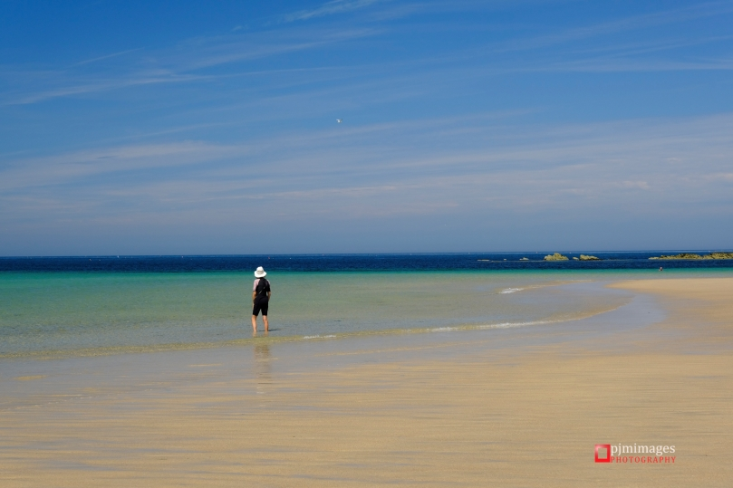 Woman in white hat paddling in the shallow water on Godrevy beach in Cornwall