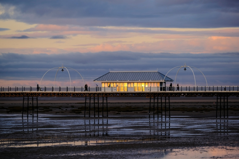 The setting sun reflected in the windows of a shelter on Southport Pier