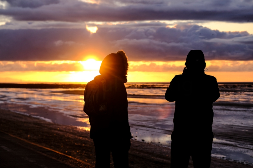 A couple watching the sun set on the coast at Southport in North-West England.
